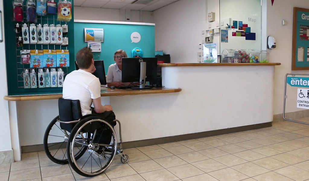 photo of wheelchair user at lowered counter reception