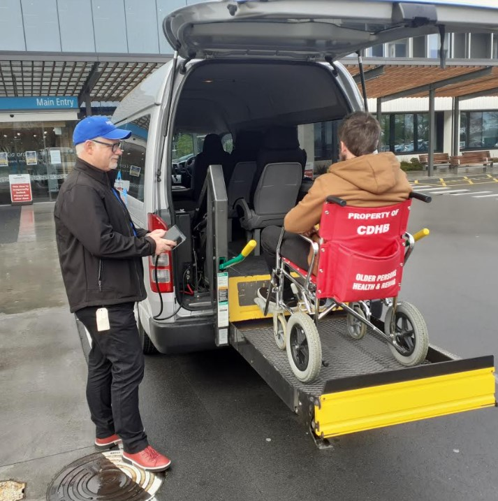 man raising wheelchair user into freedom mobility vehicle
