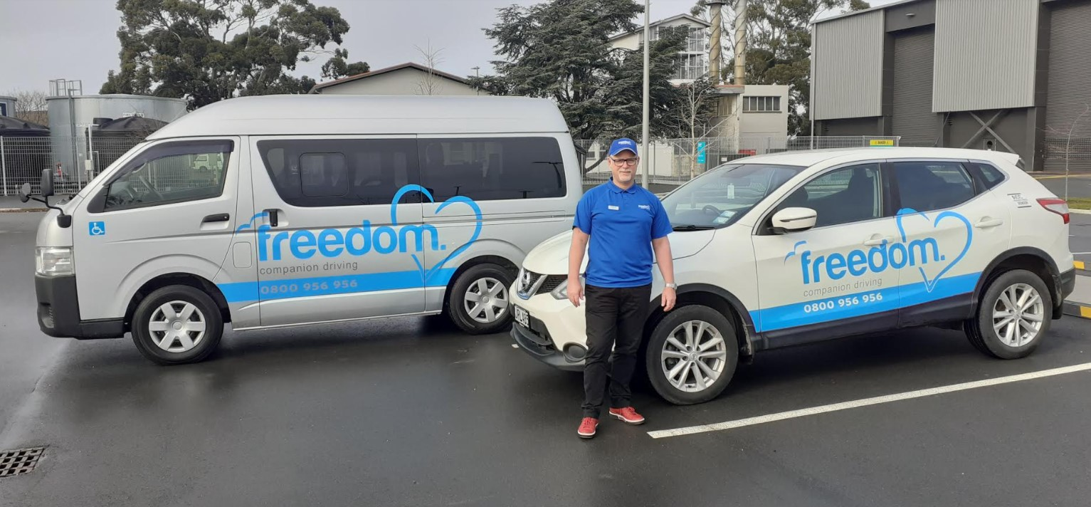 man standing beside two freedom mobility vehicles