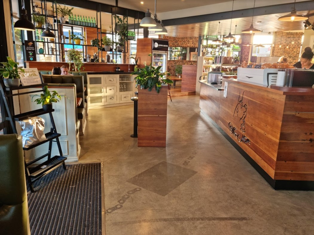 entrance to cafe including marble floor wooden counter tops and a few plants